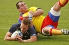 Mike Blair of Scotland scores a try in the tackle of Daniel Carpo of Romania. Photo / Getty Images