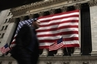 A man walks in front of the New York Stock Exchange in New York City, where stocks plunged on Friday. Photo / AFP