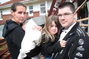 Kirstyn and Mark Hackett with baby Bastian and Elise, 3, outside their tornado-hit home in Avondale. Photo / Richard Robinson