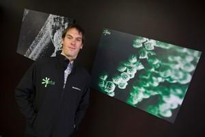 Revolution Fibres' Iain Hosie, with a blow-up of spores trapped in a nano-fibre mat. Photo / Paul Estcourt