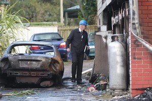 A fire inspector at the Slacks Creek house fire where 11 people died. Photo / Courier Mail