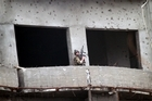 A soldier, part of the coalition forces, holds his weapon during a gun battle with Taliban militants in a building in Kabul. Photo / AP