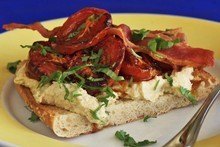 Slow roasted tomatoes on toasted panini with hummus topped with crisp bacon and coriander. Photo / NZ Herald