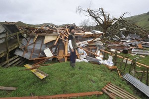 Craig Ferris and whats left of the woolshed on the Pehiri Rd Farm he works on. Photo / Gisborne Herald