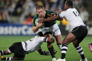 South Africa's Frans Steyn attempts to break the tackle of Fiji's Waisea Luveniyali and Seremaia Bai. Photo / Mark Mitchell