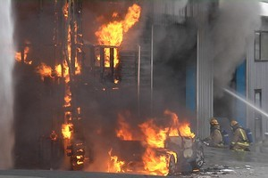 Firefighters attempt to dampen down a factory blaze in Ranui, West Auckland today. Photo / Murray Job