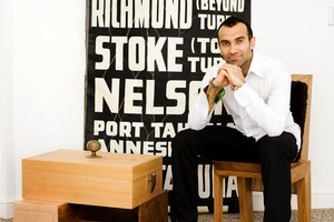 Khalid Shafar in his home with two of his hand-crafted furniture pieces. Photo / Babiche Martens