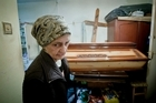 Elena Stancu, 75, keeps the coffin and cross she bought from savings in her tiny apartment. Photo / AP