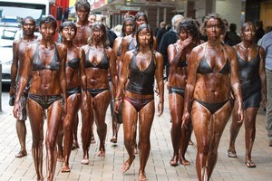 Greenpeace volunteers, covered in fake oil (molasses and water), walking along Lambton Quay in Wellington during their protest over Government's planned development of new oil and coal reserves. Photo / Mark Mitchell