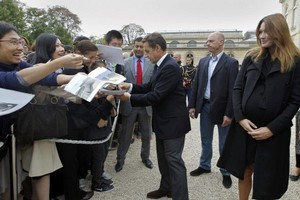 A heavily-pregnant Carla Bruni-Sarkozy (R) looks on as her husband, French President Nicolas Sarkozy, signs autographs in the gardens of the Elysee Palace in Paris. Photo / AFP