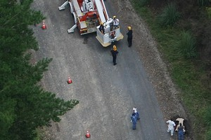 Crime scene investigators make a detailed search of Hangapipi Rd. Photo /Greg Bowker