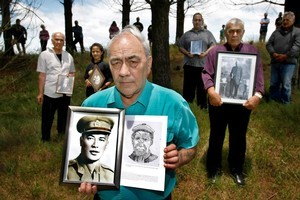 Lou Paul (front) holds pictures of his father, Uramao Otene Paora Kawharu, and his great-great-grandfather, Paora Kawharu, at Woodhill State Forest to demonstrate Te Taou's historic ties to the disputed land. Picture / Steven McNicholl
