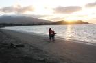 Sunsets in Raglan send a golden pathway to Ocean Beach amd silhouette Mt Karioi. Photo / Paul Rush