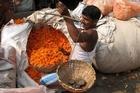 A vendor weighs a purchase of marigolds at Kolkata's Malik Ghat flower market. Photo / Jill Worrall
