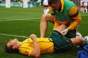 Drew Mitchell of the Wallabies lies on the ground injured and receives medical attention. Photo / Getty Images