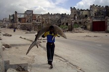 A man carries a shark through the streets of Mogad