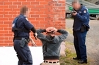 Armed officers prepare to take into custody one of the 10 people arrested. Photo / Otago Daily Times