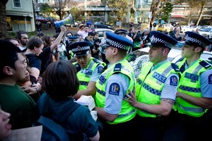 Protesters surround a police car after a student was arrested during an occupation of the sixth floor of the Owen Glenn Building at the Auckland University. Photo / Dean Purcell