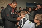 Manu Vatuvei of the Warriors signs his autograph for fans as he arrives home at Auckland International Airport. Photo / Getty Images