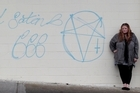 Bucklands Beach resident Lisa van der Walt is upset with how long it has taken the council to remove satanic graffiti from the wall of the Priestley Drive Superette. Photo / Richard Robinson