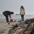 Locals work to remove oil from the Papamoa coastline. Photo / Joe Dowling
