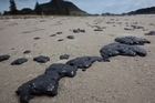 Oil from the stricken ship, Rena, has begun washing up on the beach at Mount Manguanui. Photo / SNPA/John Cowpland