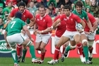 Wales' Mike Phillips leads the charge against Ireland's Sean O'Brien. Photo / Mark Mitchell