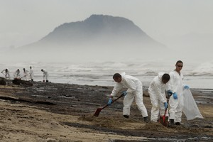 Army personnel pictured at work cleaning up the latest oil spill to hit Papamoa Beach from the Rena today. Photo / Alan Gibson
