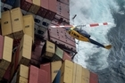 A helicopter transported salvage workers to and from the stricken container ship Rena yesterday. Photo / Alan Gibson