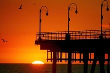 The sun sets over the Pacific Ocean at the end of Santa Monica pier. Photo / New Zealand Herald