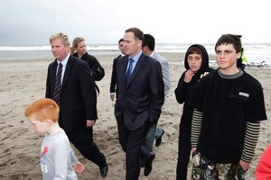 Prime Minister John Key (centre) and Rotorua MP Todd McClay are joined by local children during their visit to the Maketu Estuary near the Rena oil spill.  Photo / Mark Mitchell
