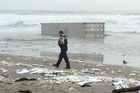 A police officer patrolling Mount Maunganui beach after containers washed up on the shore. Photo / Hayden Donnell