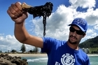 Kasey Whangapirita from Rotorua gets a close look at oil that has washed up on Mt Maunganui beaches. Photo / Alan Gibson