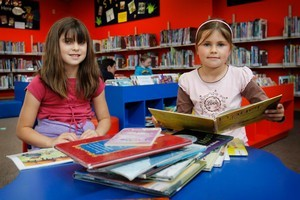 Olivia May, 9 (left), and sister Sarah, 7, enjoy reading at the Chartwell Library. Photo / Christine Cornege