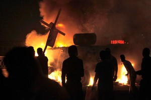 Coptic Egyptian demonstrators, one carrying a wooden Christian cross, set on fire an army vehicle during cashes with Egyptian army soldiers. Photo / AP