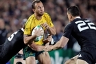 Australia's Quade Cooper eyes a tackle by Sonny Bill Williams. Photo / Sarah Ivey