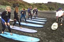 Learners work on their stance under the watchful eyes of their teachers at Raglan Surfing School, Ngarunui Beach. Photo / Derek Flynn