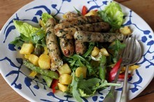 Chicken sausage on a bed of rocket, kos, red and yellow peppers and fried potato cubes; olive oil and a side of vinegar dressing. Photo / Herald on Sunday