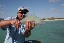 Brett Wolf holds the queenfish before releasing it. Photo / Geoff Thomas