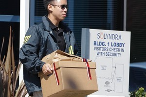 An FBI agent carries a box of evidence from Solyndra headquarters. Photo / AP
