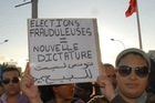 Tunisians hold up a banner reading 'Fraudulent Elections, New Dictatorship' during a protest against the moderate Islamic party Ennahda. Photo / AP