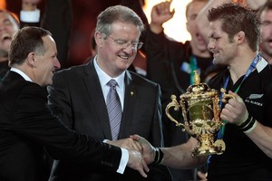 All Blacks captain Richie McCaw (R) receives the Webb Ellis Cup from IRB chairman Bernard Lapasset (C) and New Zealand Prime Minister John Key (L). Photo / Brett Phibbs