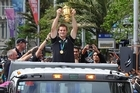 Richie McCaw, the All Blacks captain, shows the Webb Ellis Cup to the massed crowds during the team's Rugby World Cup celebration parade in Auckland. Photo / Getty Images