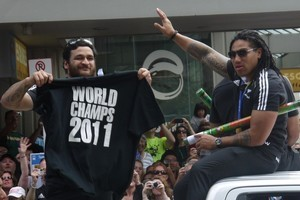 Piri Weepu (L) and Ma'a Nonu salute the thousands of people who turned out to view the All Blacks' Rugby World Cup victory parade. Photo / Troy Rawhiti-Forbes