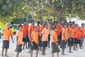 A choir of school children welcomes visitors to Pele. Photo / Isobel Marriner