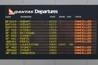 A departures screen shows all Qantas flights as cancelled in Melbourne. Photo / Getty Images