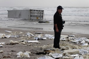 A man looks around at all the meat packs washed ashore from the grounded  ship Rena, on Mt Maunganui Beach.Photo / Mark Mitchell