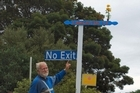 Trevor Norton and his DIY job for his street sign - complete with flower pot. Photo / Oamaru Mail