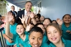 Phil Goff with Henderson North pupils yesterday after launching Labour's policy on children. Photo / Dean Purcell