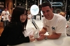 Ami Yang buys her iPhone4 S from All Black Dan Carter at Telecom's Victoria St store in central Auckland early today. Photo / Greg Bowker